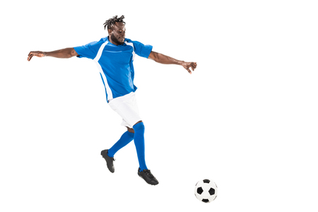Full length view of athletic african american soccer player hitting ball isolated on white 写真素材
