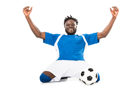 Excited african american soccer player triumphing and raising hands isolated on white