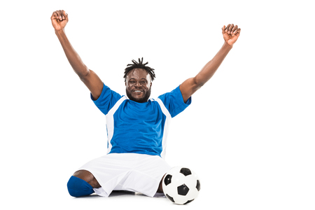 Excited african american soccer player triumphing and smiling at camera isolated on white 版權商用圖片
