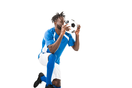 African american sportsman kneeling and holding soccer ball isolated on white Banco de Imagens