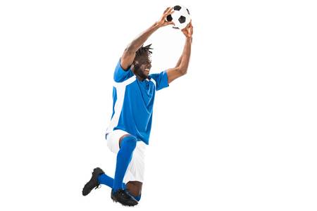 Happy african american sportsman kneeling and holding soccer ball isolated on white Banco de Imagens