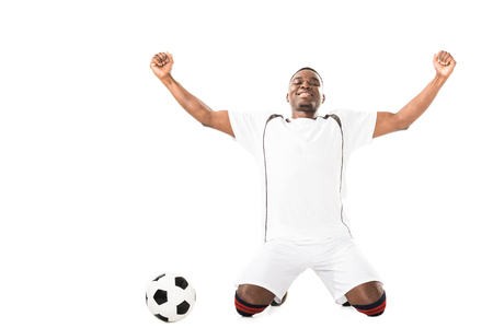 Happy young triumphing african american soccer player kneeling near ball isolated on white
