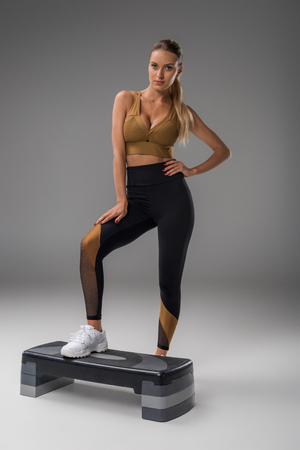Sportive young woman with aerobics step board on grey