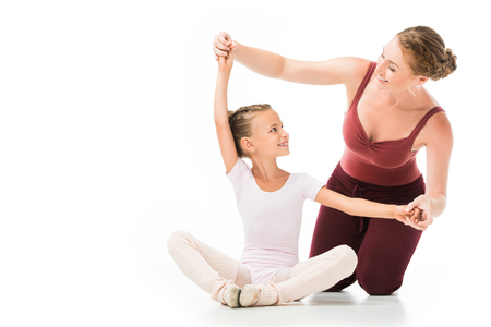 Happy female trainer helping little kid exercising isolated on white background Banque d'images