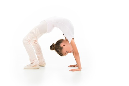 Side view of little kid performing gymnastics bridge isolated on white background Фото со стока
