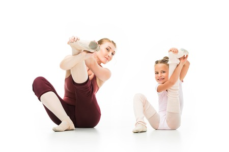 Happy little ballerina and her female trainer stretching legs isolated on white background