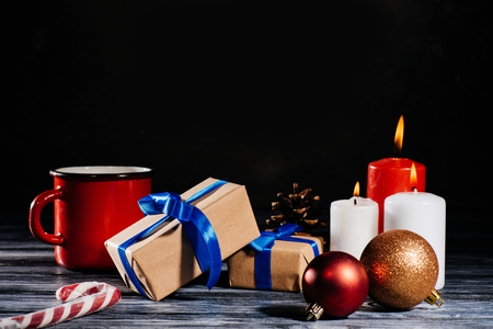 Close-up view of burning candles, pine cone, christmas balls and gifts on wooden table on black