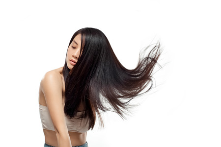 Portret van jonge Aziatische vrouw met mooi en gezond haar dat op wit wordt geïsoleerd