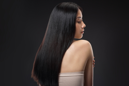 Back view of beautiful asian woman with straight and shiny hair isolated on black