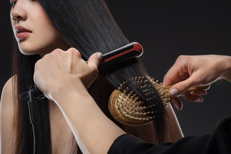 Partial view of hair stylist straightening woman hair with hair straightener and brush isolated on black
