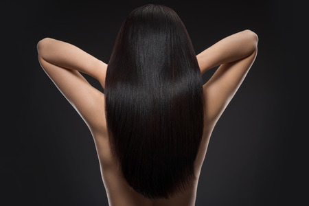 Back view of woman with beautiful shiny hair isolated on black 版權商用圖片