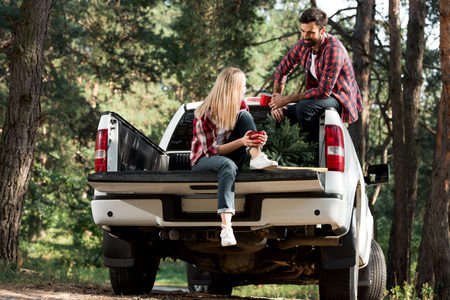 Cheerful young couple with cups sitting in car trunk with christmas tree in forest Stock Photo