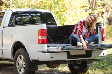 Happy attractive woman sitting in trunk of pick up car outdoors