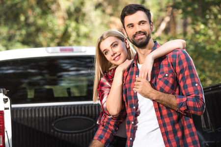 Selective focus of young couple embracing each other on car trunk outdoors