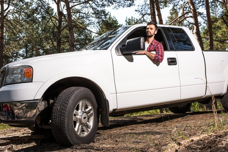Selective focus of young handsome man sitting in pick up car in forest