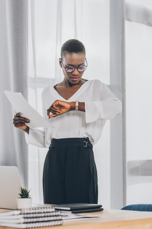 stylish attractive african american businesswoman holding documents and checking time in office