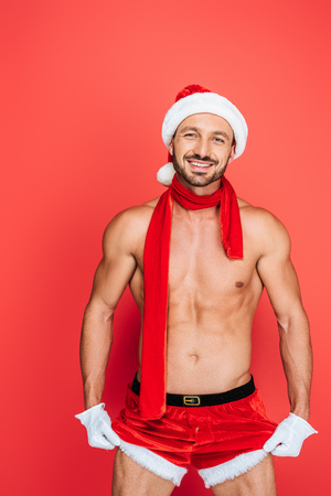 smiling muscular shirtless man in christmas hat and red scarf touching own shorts isolated on red background Stock Photo