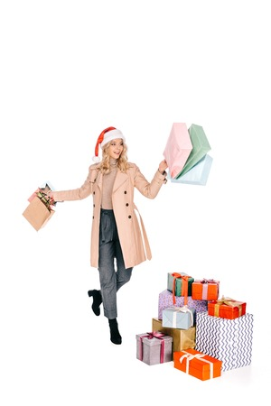 cheerful young woman in santa hat holding shopping bags and walking near christmas presents isolated on white