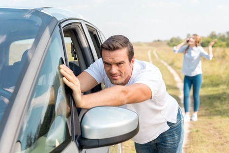 man pushing broken car while his wife talking by phone in field during car trip