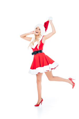 smiling young woman in santa dress and christmas hat standing on one leg isolated on white background