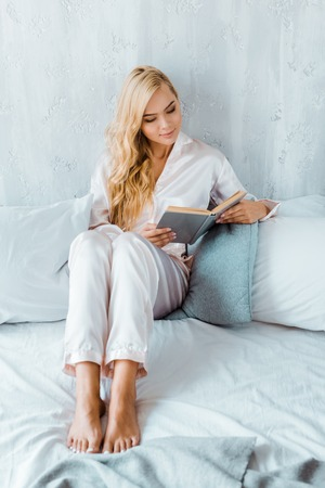 high angle view of beautiful young woman in pajamas sitting on bed and reading book