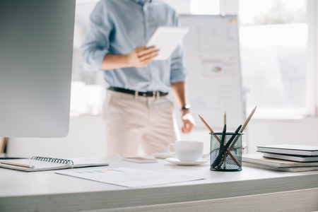 cropped image of architect using tablet in office with pen holder on foreground