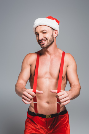 smiling shirtless muscular man in christmas hat winking holding suspenders isolated on grey background