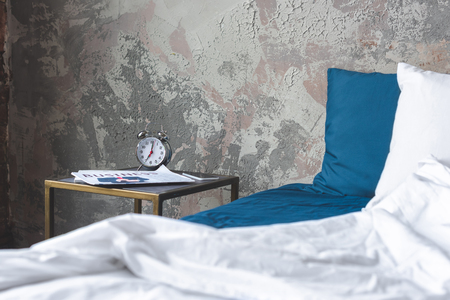 messy bed in loft bedroom with vintage alarm clock and newspaper on bedside table Stock Photo - 111267854