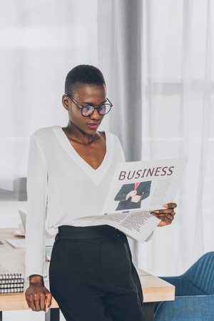 stylish attractive african american businesswoman leaning on table and reading newspaper in office Stock Photo