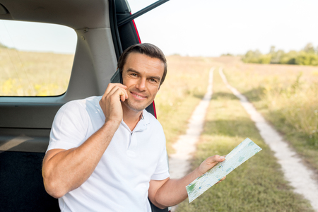 handsome man sitting in car trunk with map and talking by phone in field