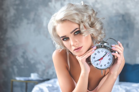 close-up portrait of attractive young woman holding vintage alarm clock and looking at camera 스톡 콘텐츠