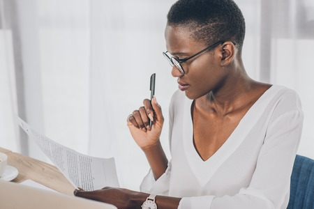 stylish attractive african american businesswoman holding pen and reading documents in office