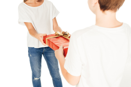 cropped image of boy presenting gift box to child isolated on white