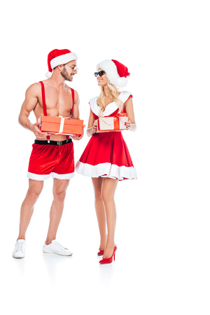 young couple in christmas hats and sunglasses holding gift boxes and looking at each other isolated on white background
