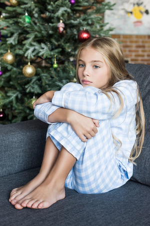 upset child in pajamas sitting on sofa at christmas time