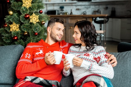 smiling couple with coffee cups sitting on sofa under blanket near christmas tree at home