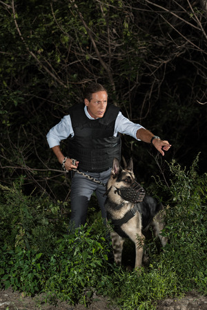 mature policeman in bulletproof vest pointing by finger to german shepherd dog near forest