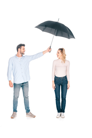 handsome young man holding umbrella above smiling young woman isolated on white