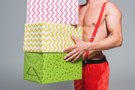 cropped image of muscular man in christmas hat holding pile of gift boxes isolated on grey background