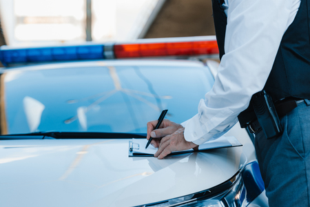 cropped image of male police officer writing in clipboard on car at street