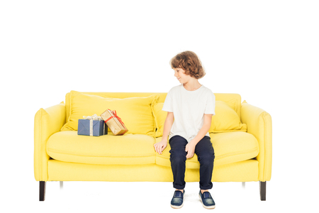 adorable boy sitting on yellow sofa and looking at gift boxes isolated on white