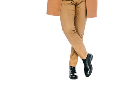cropped shot of man in stylish pants, leather shoes and brown overcoat standing isolated on white Stock Photo