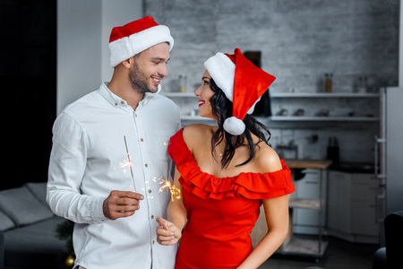 happy young couple in christmas hats with sparkles looking at each other at home Stock Photo