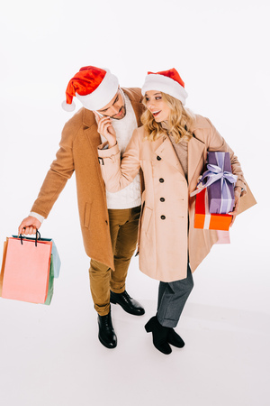 high angle view of happy young couple in santa hats holding gift boxes and shopping bags isolated on white