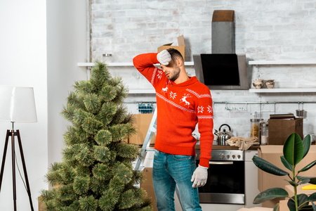 tired man in working gloves wiping forehead near christmas tree in kitchen at home Stock Photo