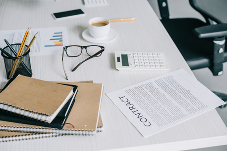 notebooks, contract and calculator on table in light modern office