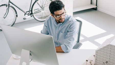 handsome architect using computer and looking at architecture model in office