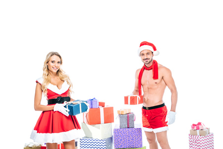 beautiful young woman in santa dress and muscular shirtless man in christmas hat giving presents isolated on white background Stock Photo