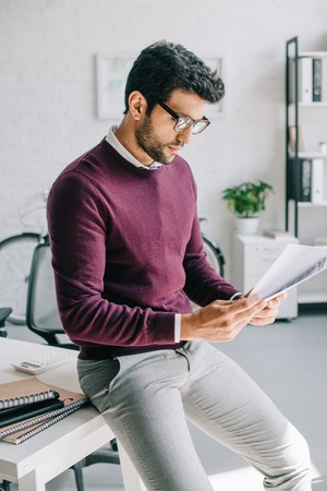 handsome designer in burgundy sweater leaning on table and reading documents in office
