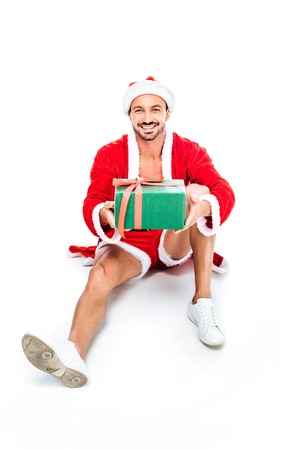 happy muscular man in santa costume sitting on floor and giving christmas gift box isolated on white background